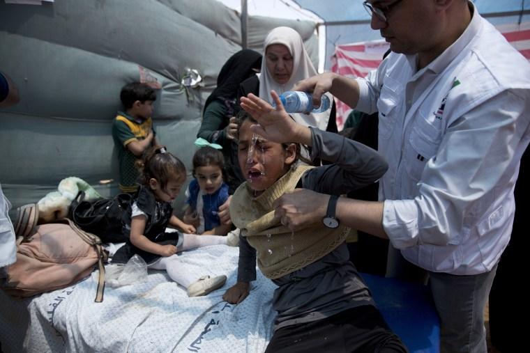 Image: Medics treat Palestinian children suffering from tear gas inhalation
