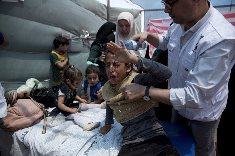 Image: Medics treat Palestinian children suffering from tear gas inhalation
