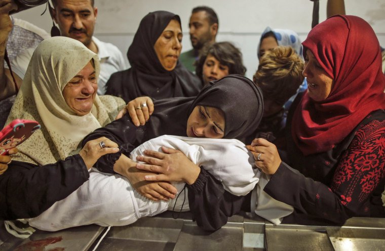 Image: The mother of a Leyla al-Ghandour holds the body of her daughter