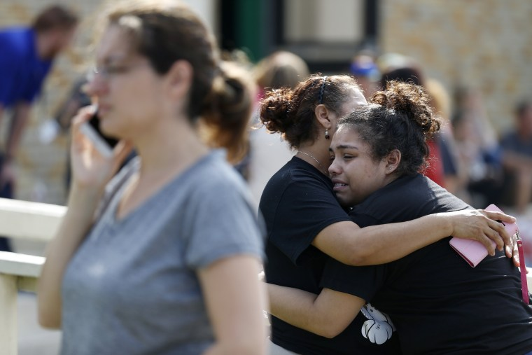 Santa Fe High School junior Guadalupe Sanchez, 16, cries in the arms of her mother, Elida Sanchez, after reuniting with her at a meeting point at a nearby Alamo Gym fitness center.