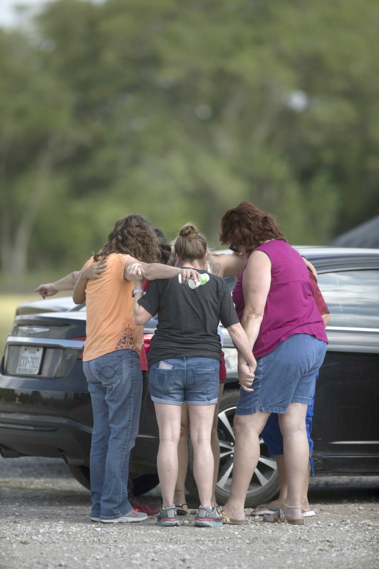 Parents of Santa Fe High School students join in prayer at the parking lot of the Arcadia First Baptist Christian School, accompanied by residents.