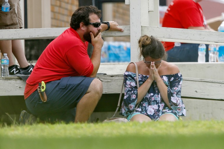 A woman prays in the grass while parents wait to reunite with their kids.