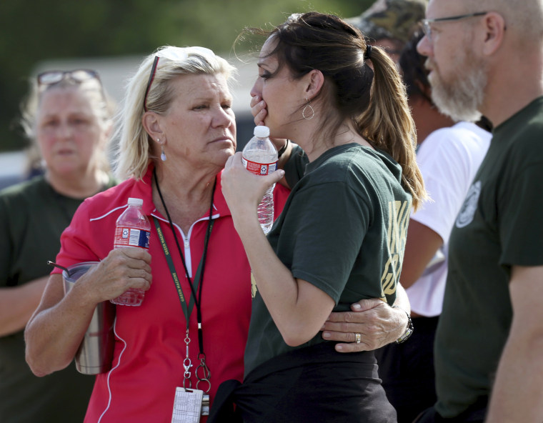 Staff react as they gather in the parking lot of a gas station following the shooting.