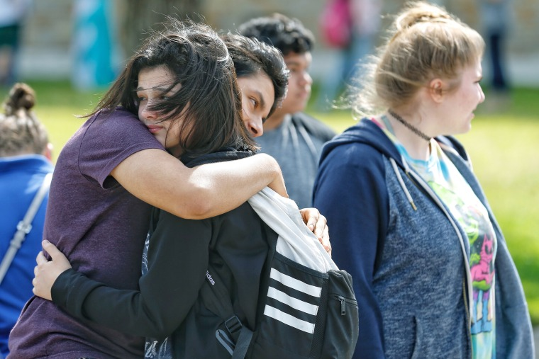 Freshman Caitlyn Girouard, center, hugs her friend outside the Alamo Gym, where students and parents wait to reunite following the shooting.