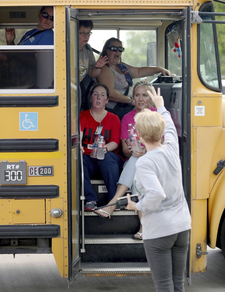 School staff members sit in a school bus to be transported to another school.