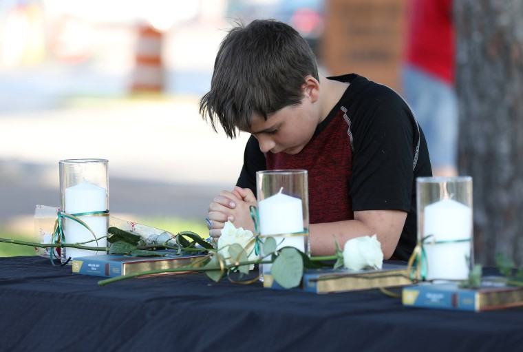 Image: A young boy prays during a vigil held at the Texas First Bank after a shooting left several people dead at Santa Fe High School in Santa Fe, Texas