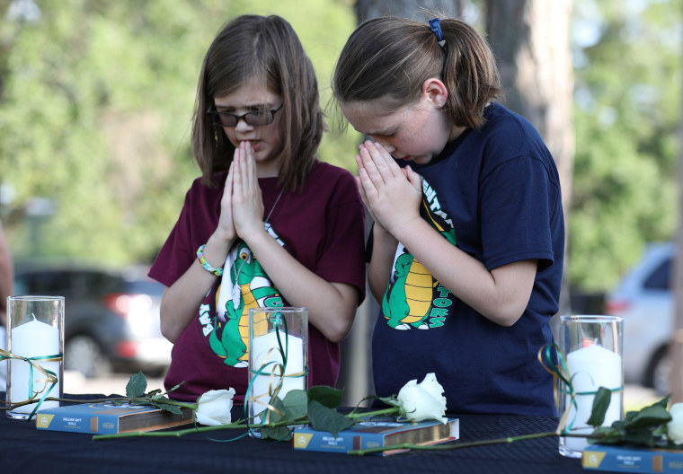 Image: Two young girls prays during a vigil held at the Texas First Bank after a shooting left several people dead at Santa Fe High School in Santa Fe, Texas