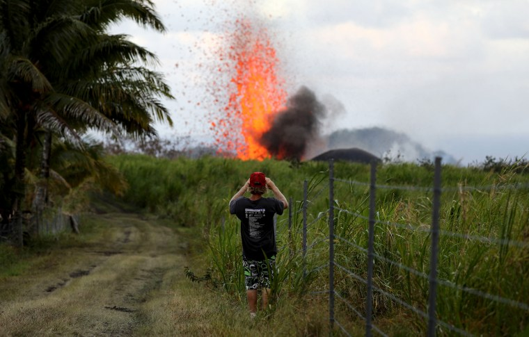 Image: A man takes a photo of a lava fountain from a Kilauea volcano fissure on Hawaii's Big Island on May 18, 2018 in Kapoho, Hawaii.