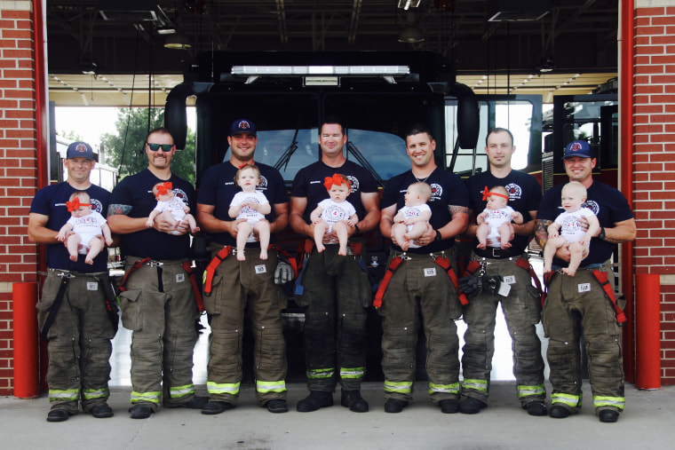 Seven firefighters with their babies pose for picture