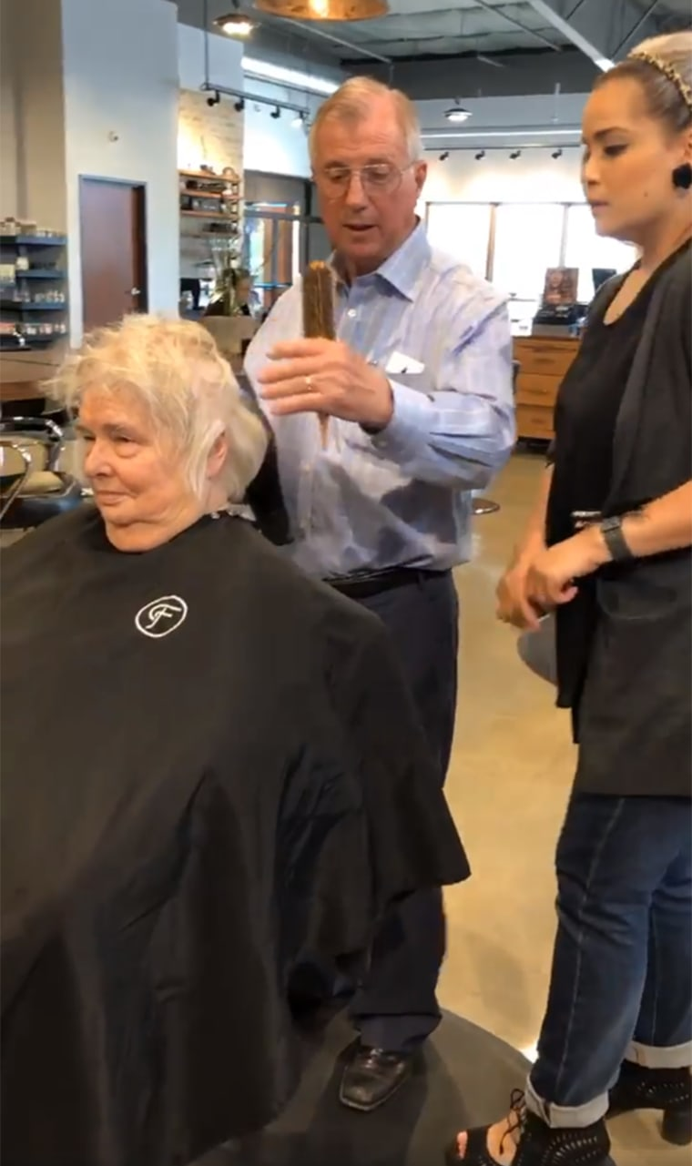 Man styles his wife's hair