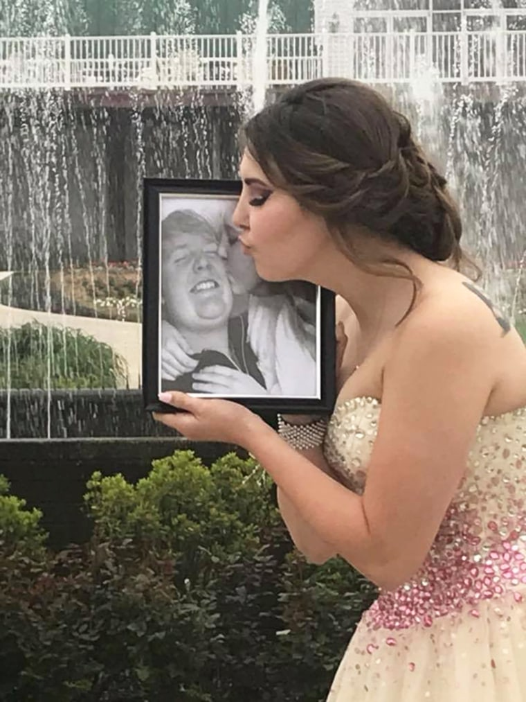 Kaylee offers a kiss to a photo of Carter on prom night.