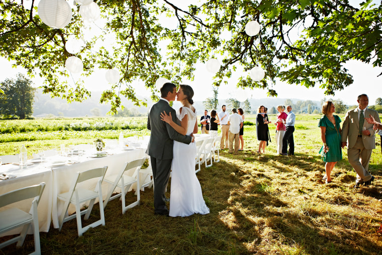 Bride and groom kissing outside