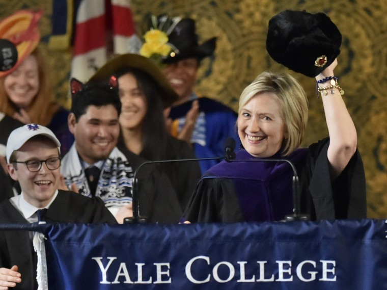 Hillary Clinton holds up a Russian fur hat at Yale