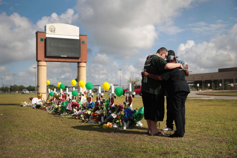 Image: Mourners pray at a memorial in front of Santa Fe High School