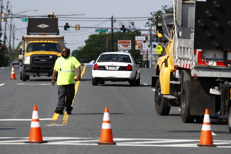 Image: An emergency vehicle passes a roadblock near a scene where a Baltimore County police officer died