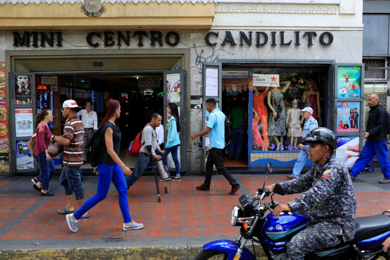 Image: People walk past stores in downtown Caracas