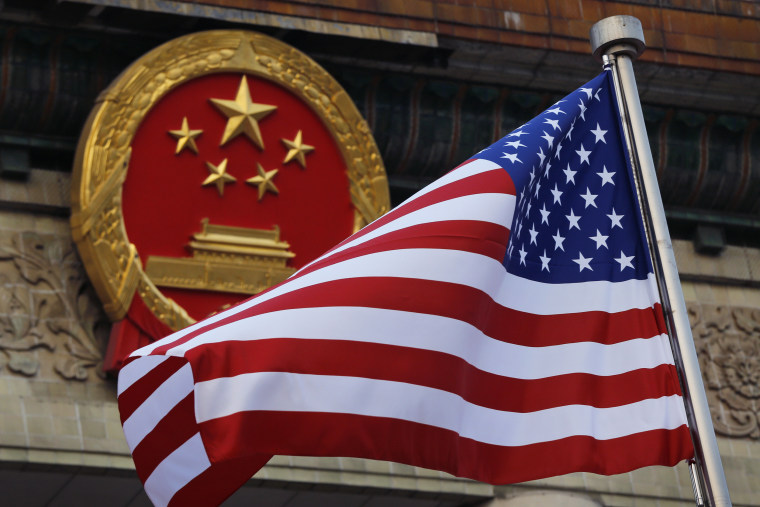 Image: An American flag is flown next to the Chinese national emblem