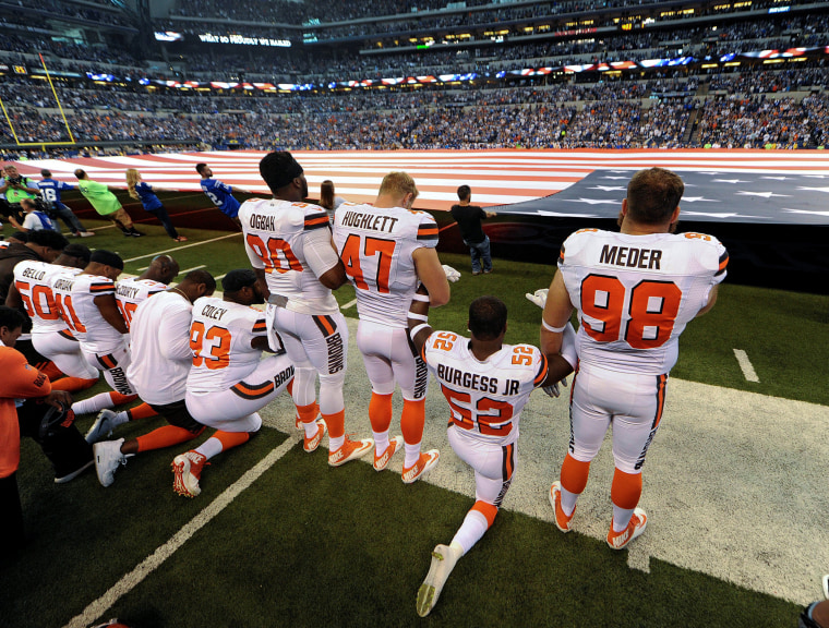 Image: Some members of the Cleveland Browns team kneel during the National Anthem