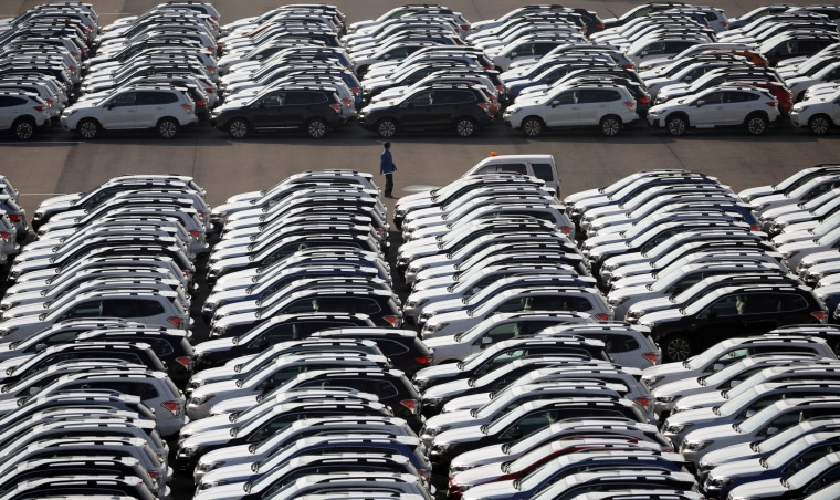 Image: A worker is seen among newly manufactured cars awaiting export at port in Yokohama