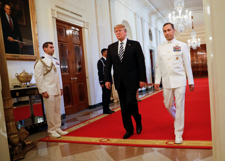 Image: Donald Trump arrives with retired Navy Master Chief Special Warfare Operator (Sea, Air, and Land) Britt Slabinski to an award ceremony for the Medal of Honor