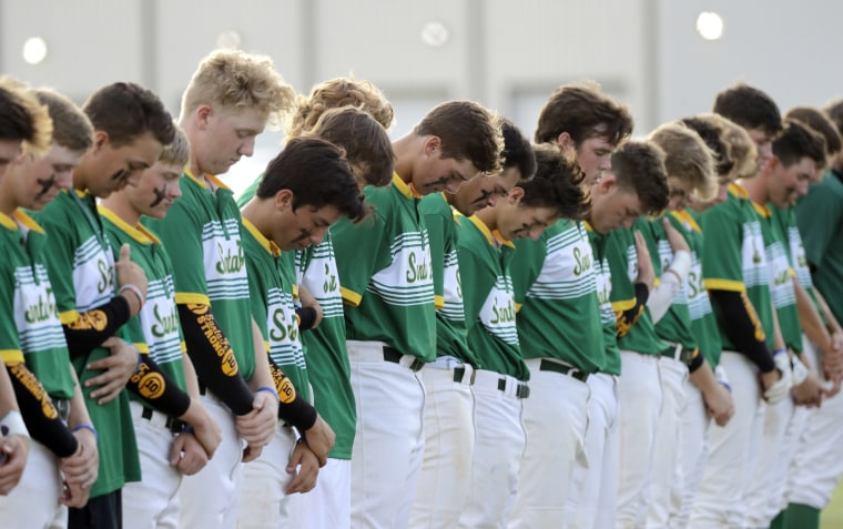 Image: Santa Fe High School baseball players bow their heads in a moment of silence for the shooting victims