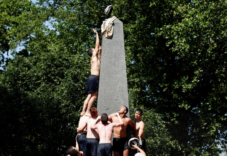 Image: A plebe places a midshipman's cap on top of the grease covered 21-foot Herndon Monument