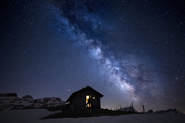 Image: A man stands inside cabin with a view of the Milky Way