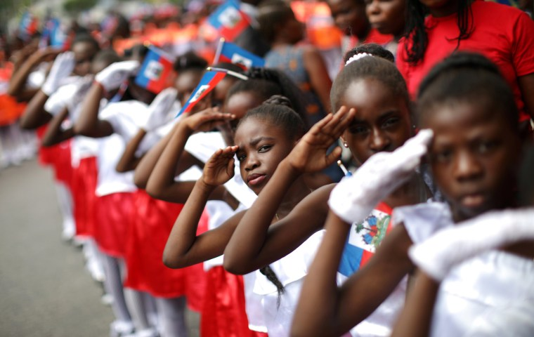 Image: Girls salute during celebrations for National Haitian Flag Day in the streets of Petion Ville, Port-au-Prince