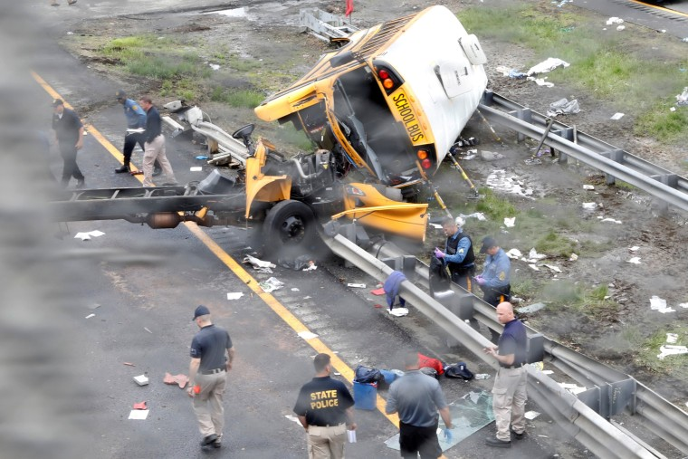 Image: Police stand near the wreckage of a school bus on Interstate 80 following an accident with a dump truck in Mount Olive Township