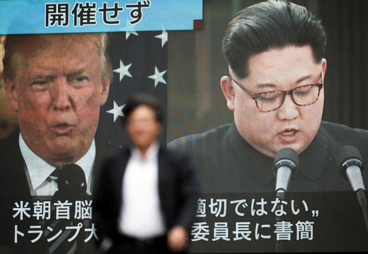 Image: A pedestrian walks in front of a screen in Tokyo on May 25, 2018 flashing a news report relating to U.S. President Donald Trump cancelling his meeting with North Korean leader Kim Jong Un.