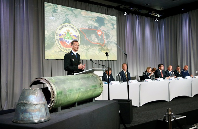 Image: Dutch police officer Paulissen is pictured next to a damaged missile as he presents interim results in the ongoing investigation of the 2014 MH17 crash, during a news conference by members of the Joint Investigation Team in Bunnik