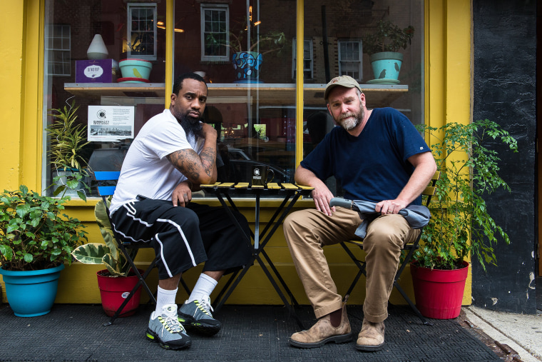 Image: Christian Dennis and Bob Logue, co-owners of Quaker City Coffee, sit outside their coffee shop in Philadelphia on May 22, 2018.