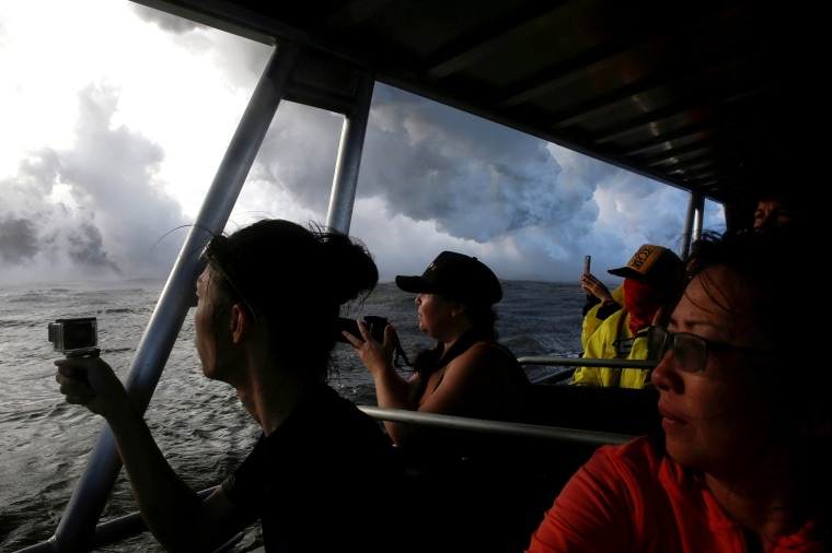 Image: FILE PHOTO: People watch as lava flows into the Pacific Ocean southeast of Pahoa