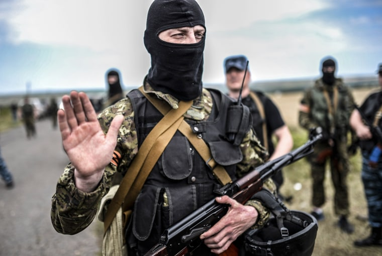 Image:An armed pro-Russian separatists gestures as he blocks the way to the crash site of Malaysia Airlines Flight MH17