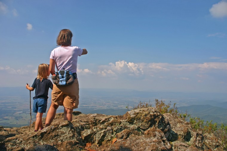 Mother with young child hiking on top of the mountains