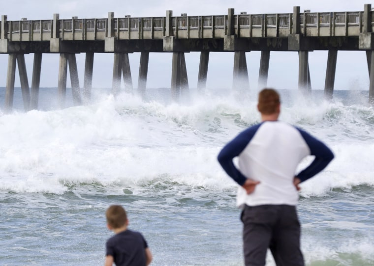 Image: Harrison Westwood, 4, and his father Ben watch waves crash in Pensacola, Florida.