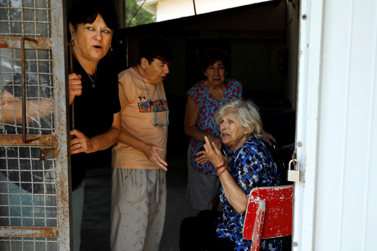 Image: Women react after a siren is sounded, in a Kibbutz on the Israeli side of the Israeli-Gaza border