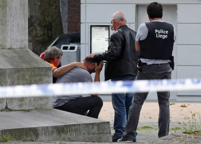 Image: A man is being consoled at the scene of a shooting in Liege
