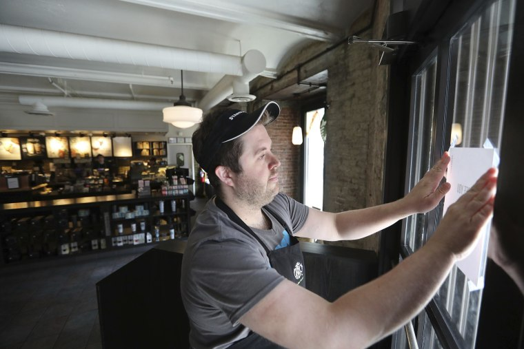 Image: Manager Alex Lair places a closed notice on the corner door at a Starbucks in Philadelphia