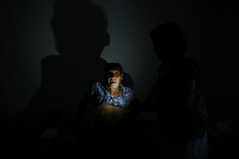Image: Cancer patient Israel Gonzalez poses for a photograph with the light of a solar lamp at his home as the island's fragile power system is still reeling from the devastation wrought by Hurricane Maria eight months ago, in Utuado