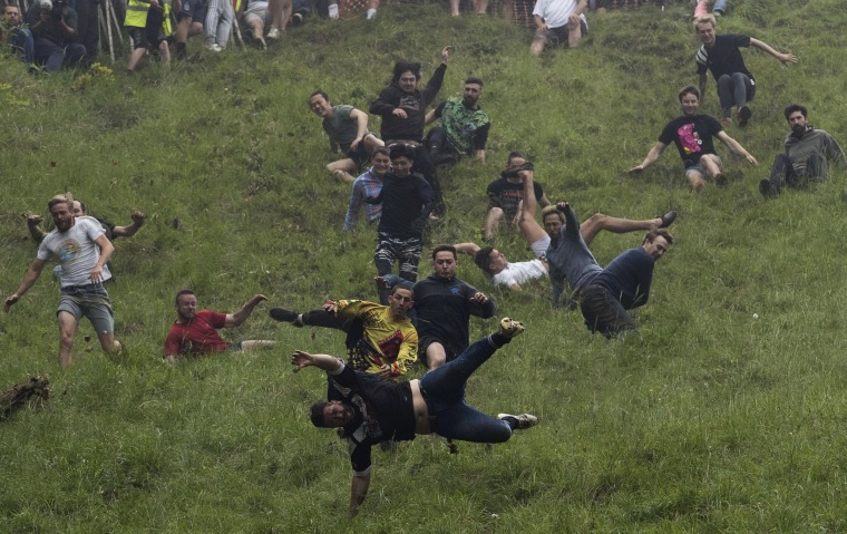 Image: Competitors take part in the annual cheese rolling competition at Cooper's Hill