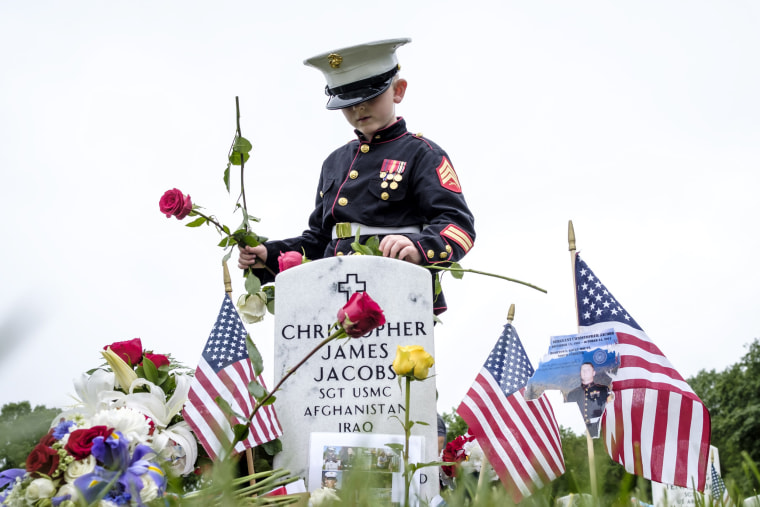 Image: Christian Jacobs tends the grave of his father at Arlington National Cemetery