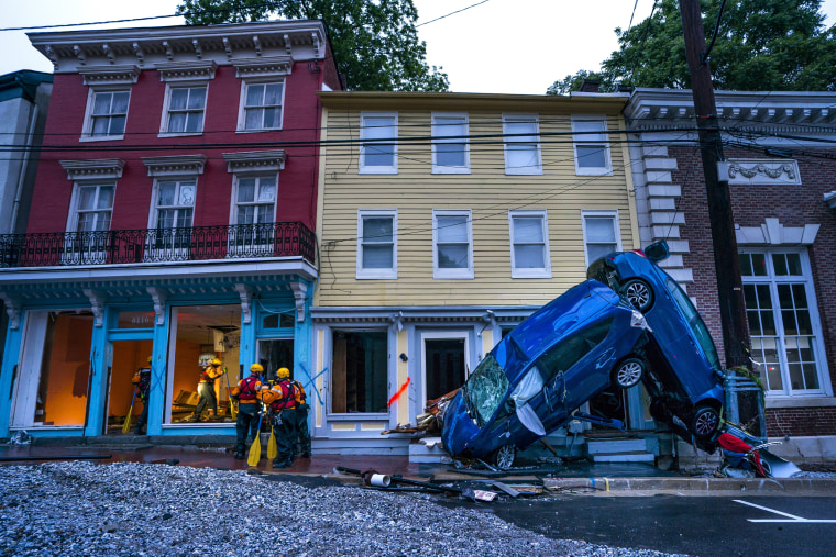 Image: Rescue personnel examine damage after roaring flash floods rushed through the historic town of Ellicott City