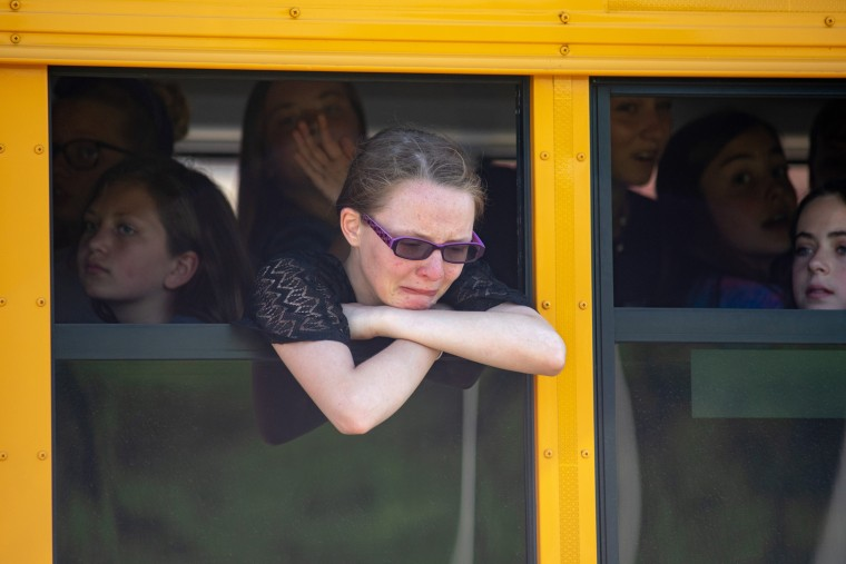 Image: Evacuated Noblesville West Middle School students wait on a bus after a shooting at the school