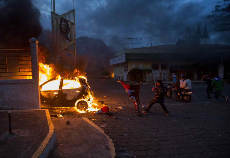Image: A man throws a flag belonging to the current ruling party towards a burning vehicle during protests in Managua