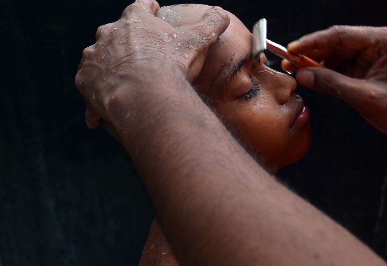 Image: A Sri Lankan novice monk has his eyebrows shaved during a ceremony marking their entry into priesthood