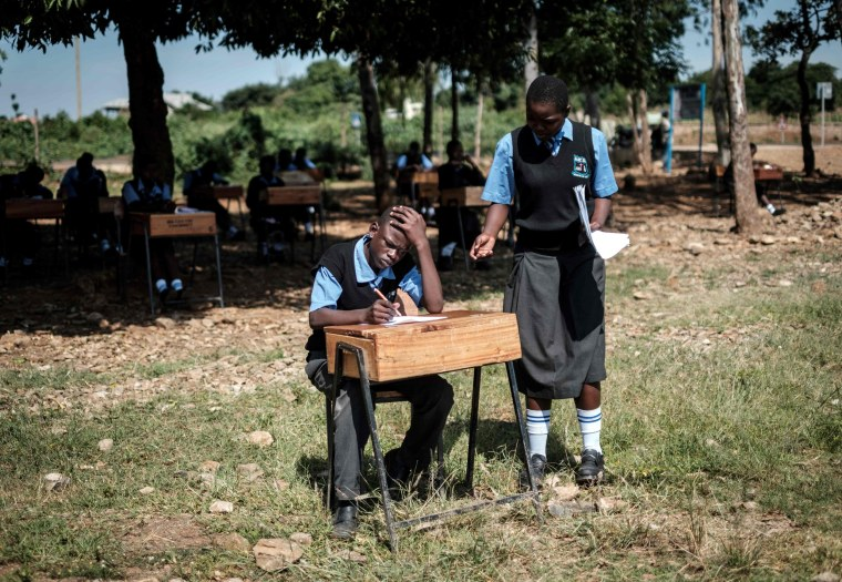 Image: Students take their English test outside because of overcrowded classrooms in Kisumu, Kenya