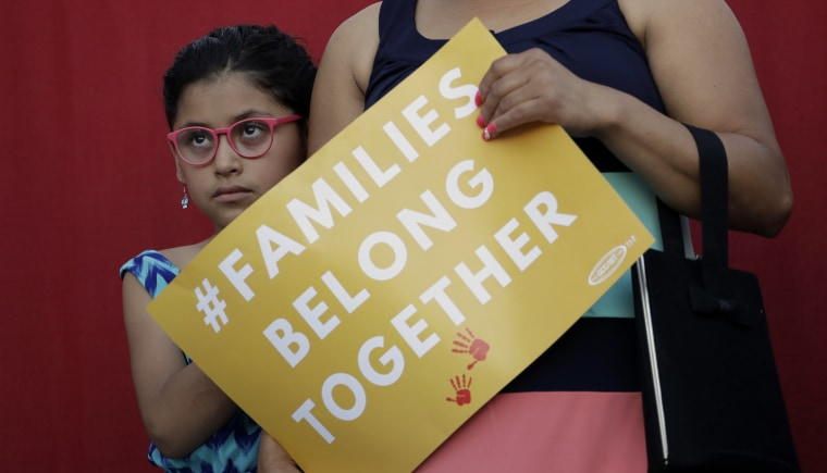 Image: A girl stands with her mother during a Rally For Our Children event in San Antonio