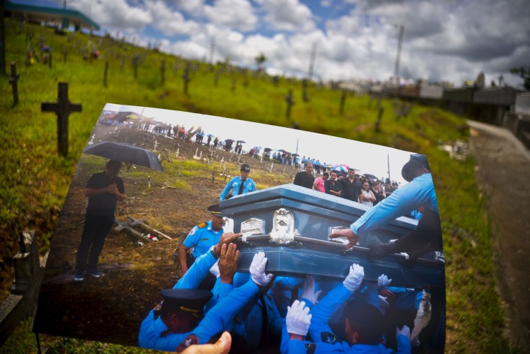 Image: A printed photo taken on Sept. 29, 2017 showing police lifting the coffin of officer Luis Angel Gonzalez Lorenzo, who was killed during the passage of Hurricane Maria when he tried to cross a river in his car, is shown at the same cemetery.