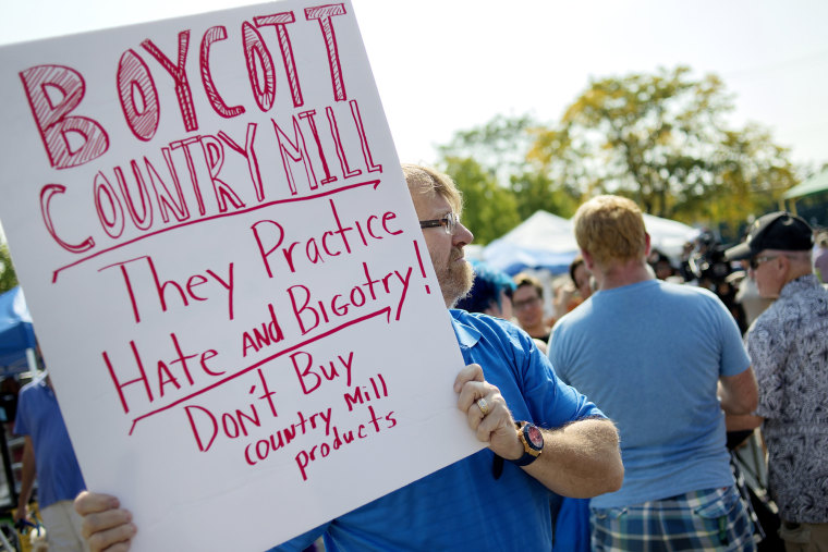 Image: Lansing resident Kennan DeWitt holds up a sign near the Country Mill booth in protest on Sunday, Sept. 17, 2017, at the East Lansing Farmer's Market.